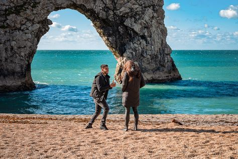 Boyfriend going down on one knee at Durdledoor sea arch and beach at secret wedding proposal photographs