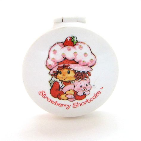 This vintage Strawberry Shortcake makeup compact has Strawberry Shortcake on the cover and has a mirror inside the lid. The compact was originally from the Berry Pretty Face Boutique set and had face cream in it, but it's now empty. You can use it to store makeup, pills, small jewelry, or anything else that will fit inside. The Berry Pretty Face Boutique set came with strawberry scented lip gloss, face cream, and cologne and items from this set are some of the more rare and hard-to-find…