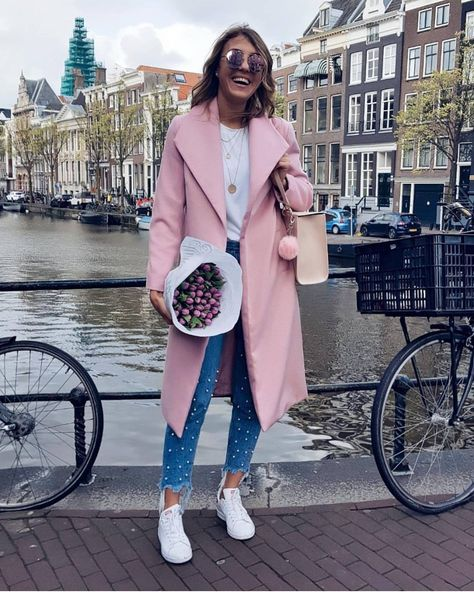 Casual spring outfit with pink coat, denim jeans and sneakers.