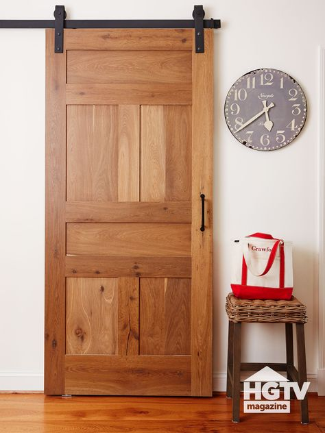 This space saver is cute too! A wooden barn door paired with a wicker stool and rustic clock gives this space total farmhouse vibes. See more ways to use barn doors on HGTV.com.