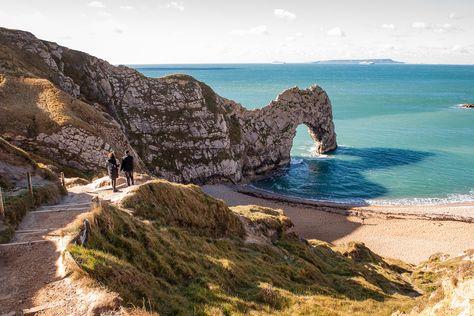 Boyfriend and girlfriend walk down to Durdledoor beach and sea arch at secret wedding proposal photo shoot