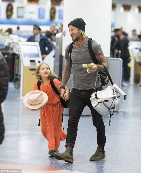 Daddy's girl: Yet David Beckham was headed home alongside his family as he returned to Miami on Thursday afternoon, where his youngest, daughter Harper, six, held him close while wife Victoria put on a typically sensational display in staggering heels