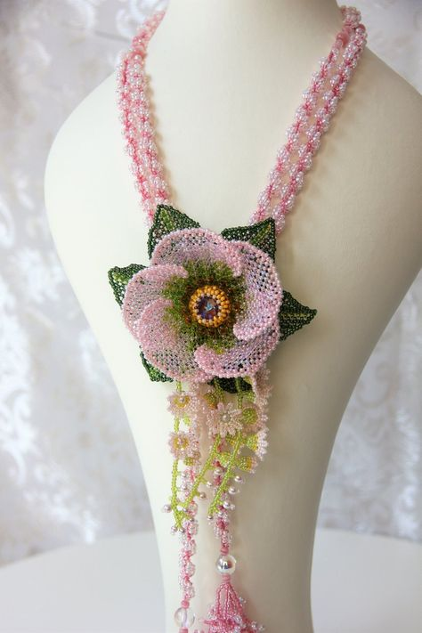 A stunning statement lariat necklace that will be a conversational piece at any event. The focal flower is embroidered with glass seed beads and measures inches in diameter.