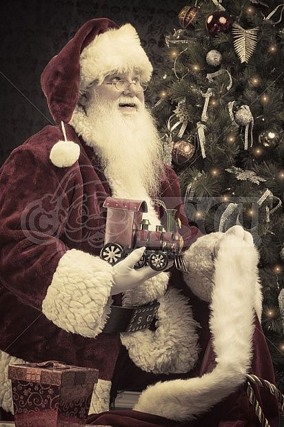 A real authentic Christmas photo of Santa Claus holding a toy train. Santa is looking up while holding a toy train that he took from his gift bag. Real Santa Pictures and This images can be licensed to use at realsantaimages.com | Do Not Use Without A License
