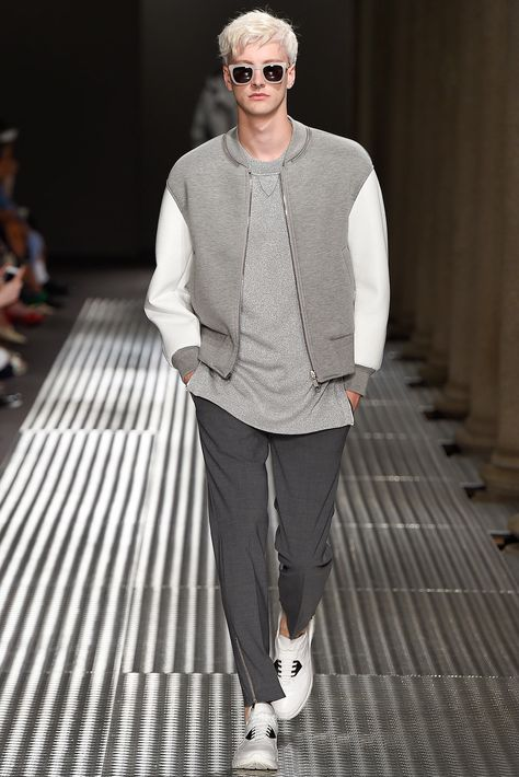 This pairing of a grey bomber jacket and charcoal dress pants can only be described as incredibly stylish and elegant. Bring a fun feel to this ensemble by wearing a pair of white and black athletic shoes.