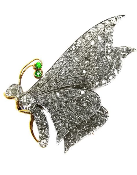 Antique diamond and demantoid garnet butterfly brooch, c.1900 , viewed in profile, the wings pave set with cushion cut diamonds, a series of larger diamonds forming the head and body, the gold antennae terminating in two demantoid garnets, gold legs, mounted in platinum and gold