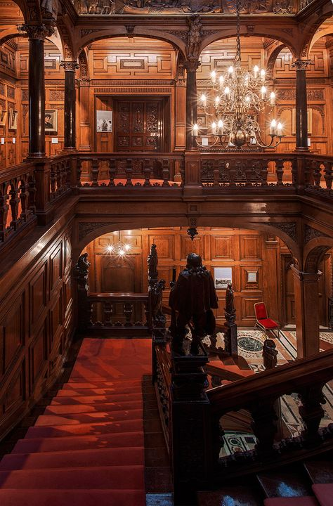 "A view down the staircase of the Astor House - an architectural marvel in London. Two Temple Place, known for many years as ""Astor House"", is a building situated near Victoria Embankment. It is both an architectural gem and a veritable treasure house of e"