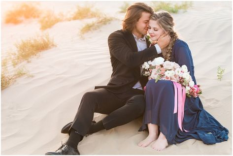 Couple dressed in black suit and blue flowy dress with white and pink orchid floral bouquet during couples session | Little Sahara Sand Dunes Milky Way Engagement Session #utahengagement #utahengagementpictures #utahengagementphotography #utahlocations #littlesahara #utahbride #utahbrideandgroom #utahcouple #utahengagementphotographer #utahengagementphotography #rockymountainengagement #adventureengagement #sanddunes #milkyway #milkywayphotography #astrophotography