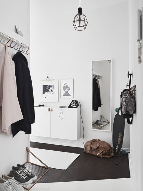 Une entrée avec différentes patères, un miroir rectangulaire sur le mur et un meuble blanc peu profond pour ranger chaussures et accessoires
