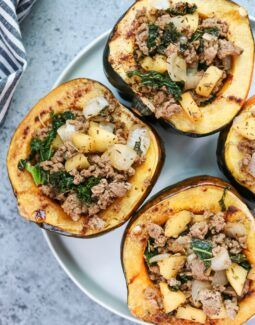 This Whole30 Harvest Stuffed Acorn Squash is a delicious sweet and savory fall dish! Roasted acorn squash get stuffed with a mixture of homemade pork sausage, onion, apples, kale, and spices. The stuffing makes a great breakfast hash, as well! #whole30 #septemberwhole30 #whole30recipes #stuffedsquash #stuffedacornsquash #squashrecipes #paleo #aip #easyrecipes #healthyrecipes
