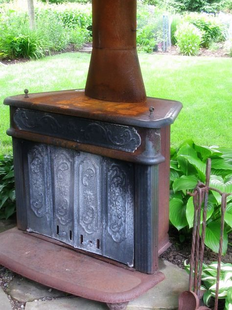 Old stove doubles as a piece of art and a fire pit in the garden.