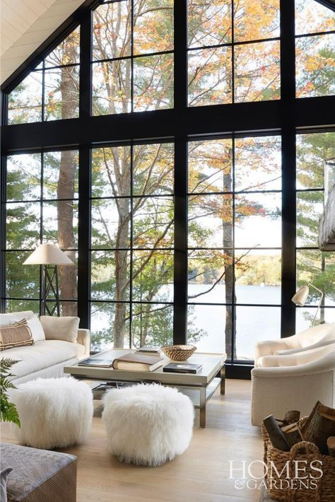 AMERICAN LAKE HOUSE LIVING ROOM WITH FLOOR-TO-CEILING FRAMED WINDOWS WITH LAKE VIEW