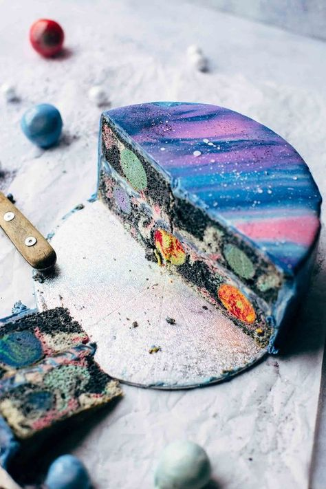 Full Mirror Glaze Galaxy Cake recipe with colorful galaxy cake pop planets, a galaxy cake, a galaxy vanilla buttercream, and a galaxy mirror glaze. Outside a shiny and colorful galaxy mirror glaze and inside a galaxy cake with four different planets.