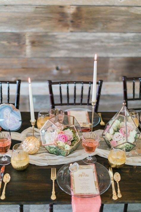 """We went for a glammed-up natural look,"" says photographer Lori Blythe. ""Gilded geode slices graced marbled menus set atop crystal-clear plates on a farmhouse table accented with a gauzy runner and geometric terrariums brimming with soft flowers."""