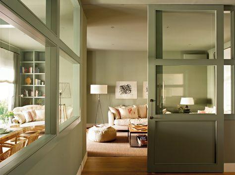Distribuidor acristalado    Lleva al espacio que comparten salón, comedor y rincón de lectura, pintado en un personal verde-gris. Puf de Coco-Mat y cuadros, en Pilar Martí Gallery.