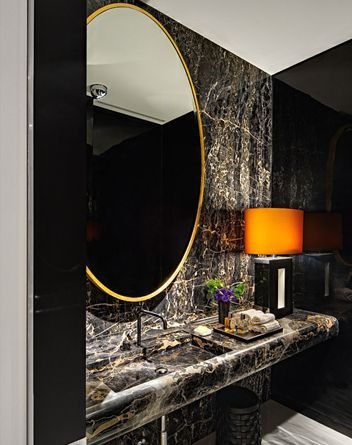 Powder Room - Love the black/white natural stone, gold framed oval mirror and the wall sconces casting a soft glow.....this is one memorable space.
