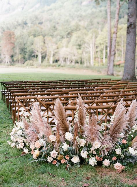 Consider these mauve-toned arrangements of pampas grass, roses, and eucalyptus, which mix desert vibes with traditional accents while flanking the aisles in this sweet mountain ceremony. Click through for more rose gold wedding ideas! #rosegoldwedding #mountainwedding #pampasgrass #aislerunners #mauvefloralarrangements