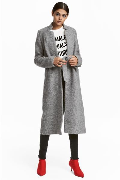 Coat in a felted wool blend with a tie belt at the waist. Small stand-up collar, side pockets, no fasteners and a single back vent.