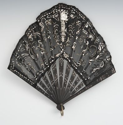 """A Black Lace & Sequined Victorian Fan, Circa 1885    Tapered shaped fan of shear black lace, backed with second shear layer, decorated with sequins, ebonized wood frame with embedded silver colored dots, with handle, 11""""L."""