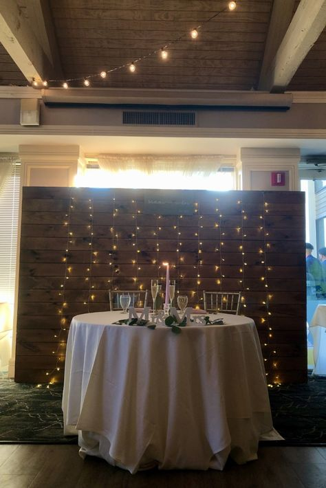 #sweethearttable #headtable #woodwall #backdrop #stringlights #candlestick #mrandmrs #simpleweddingideas #simpleweddingdecor #cleanlook #ivory #greenery #blush #springwedding #summerwedding #weddingvenue #receptionvenue #ballroom #njbride #njwedding #ronjaworskiweddings #blueheronweddings #bohowedding #woodsywedding #coastalwedding #elegantwedding #weddingideas #weddingdecorideas #diywedding #goldchiavarichair #golfcoursewedding #champagneflute #tablescape #weddingtableideas