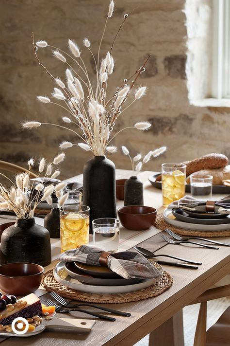 Set the scene with a dining table styled with natural textures and rich, fall colors. New dishes come in deep reds, accompanied by copper napkin rings. Finish the look with a centerpiece of dried stems in a black vase.