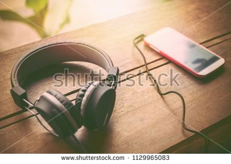 Headphones And Mobile Phones Placed On The Wood In Sunset Background