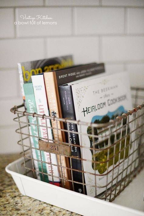 Add a vintage touch to your kitchen by tucking some of your favorite cookbooks into an antique basket for display. Via A Bowl Full of Lemons