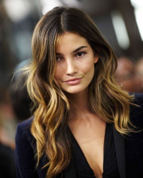 "Ombré is a French word that literally means ""shaded like a gradient."" Roots remain dark while the rest of the hair becomes lighter mid-shaft using a balayage technique. Check out this photo of model Lily Aldridge. Her dark to light color is a great example of ombré. This trend is also referred to as ""surfer strands."""