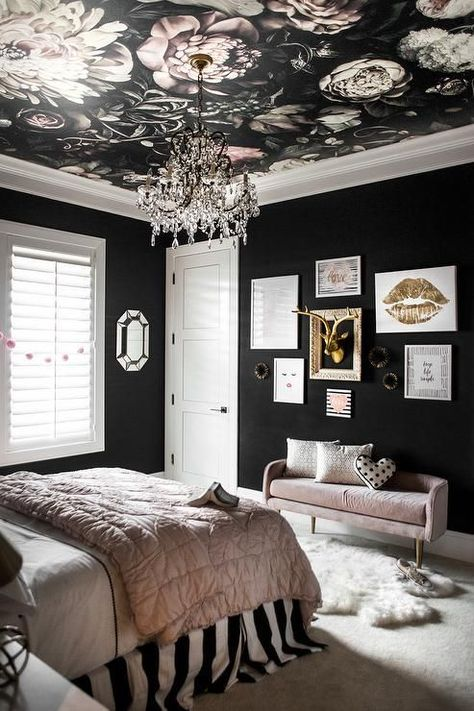 Ellie Cashman Dark Floral Wallpaper provides a bit of drama to a girl's bedroom ceiling holding a crystal chandelier over a bed dressed in pink and black bedding and a PB teen The Emily & Meritt Circus Stripe Bedskirt.