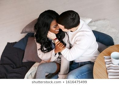 Young Interracial Couple Sitting On The Floor Hugging And Kissing