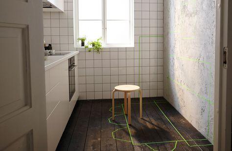 Pieni keittiö, jossa yksi seinä on jätetty paljaaksi. Tulevan kalustuksen sijainnit on merkitty vihreällä teipillä.