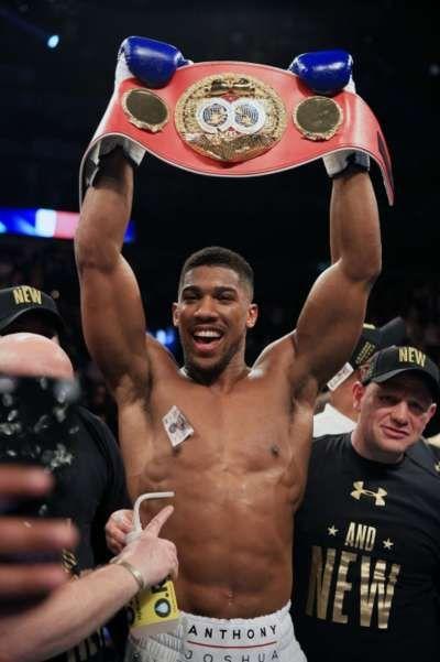 Anthony Joshua raises the belt above his head