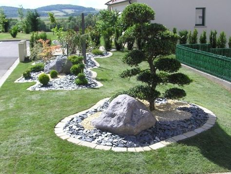 ein runder Steingarten mit grauem Kies und grünen Pflanzen - gartengestaltung mit steinen und grsern modern