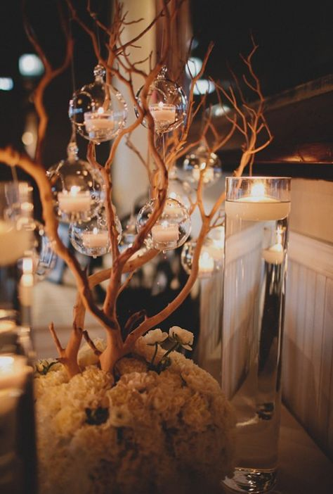 Centerpiece tree with flowers at base with hanging candles.