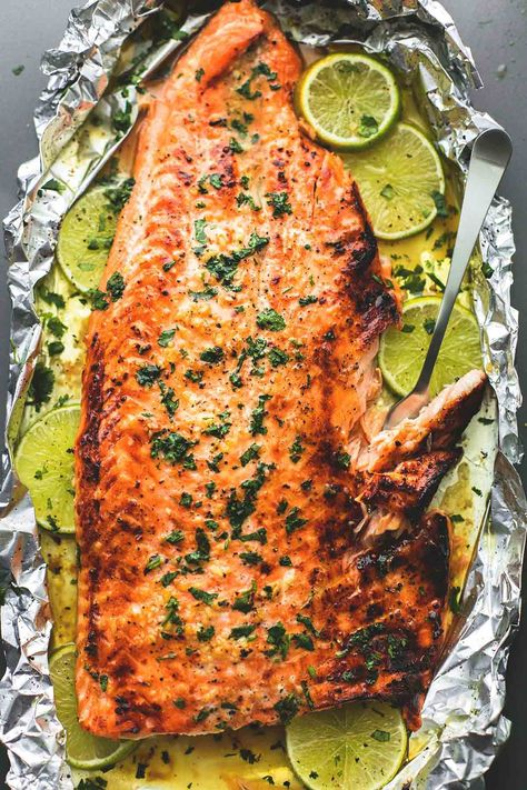 Baked honey cilantro lime salmon in foil is cooked to tender, flaky perfection in just 30 minutes with a flavorful garlic and honey-lime glaze. Check out our Savory Recipes board for our favorite food photography, dinner ideas & healthy vegetarian dishes. Salmon Dishes, Fish Dishes, Seafood Dishes, Seafood Recipes, Chicken Recipes, Cooking Recipes, Healthy Recipes, Recipe Chicken, Cooking Fish