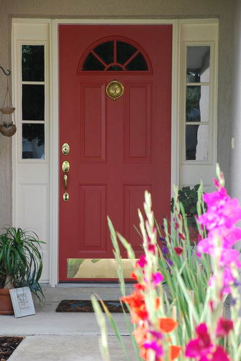 I just painted my home door here in Florida this beautiful Benjamin Moore Aura Exterior, Satin finish paint. I think Benjamin Moore has beautiful colours. This one is called Moroccan Red 1309. I love it against the gladiolas that bloom in my walk way. I added real brass accents like door accessories.