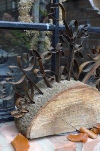 Blumenstecker aus Stahlband auf einer halben Baumscheibe