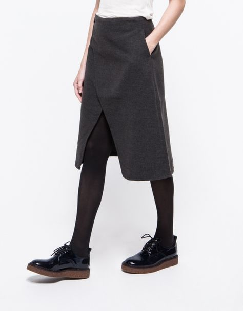 A soft mid length fleece skirt with front overlap styling. Features a front and interior button closure, front pockets and a fitted waistline.Origami Skirt make on burgundy woolOrigami Skirt - Need Supply Co.wrap skirt with interesting structural shaping
