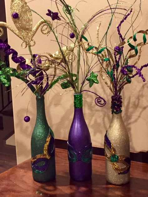 Hand painted wine bottles accented with Mardi Gras ribbon on bottle neck and filled with Mardi Gras floral decor. A sequin mask is added to each bottle for a sparkly finish. Most orders will take a week or less however more time may be needed for certain