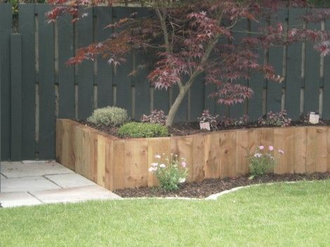 Raised Flower Bed With The Wooden Seat Built Along The Right Side Of The  Garden. Stepping Stones Laid To Allow Easy Access To The Garden.