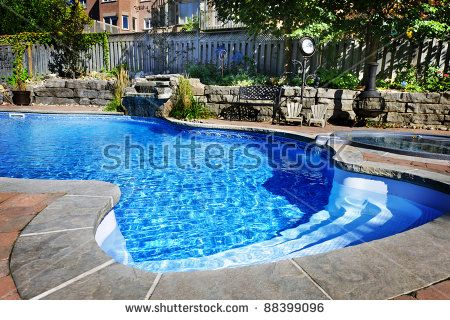 Residential Inground Swimming Pool In Backyard With Waterfall And