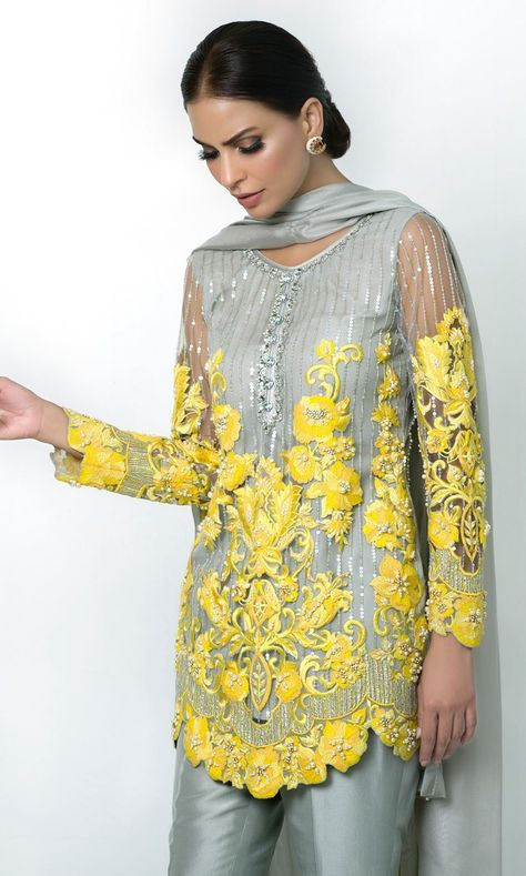 Set on a base of ash grey cotton net, this three piece ensemble features canary yellow embroidery with crystal embellishment and cutwork at the bottom. Comes with ash grey trousers in pure raw silk with crystal buttons and a net dupatta.