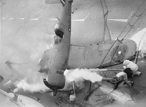FIRE-FIGHTERS OF BRITAIN'S EASTERN FLEET. NOVEMBER 1944, ON BOARD HMS ILLUSTRIOUS. SHOWING HOW THE FLIGHT DECK HANDLING PARTY (EVERY MAN A TRAINED FIRE FIGHTER) TACKLED A BLAZE WHEN A CHANCE-VOUGHT CORSAIR FIGHTER COMING IN JUMPED THE ARRESTER WIRES AND CRASHED INTO THE SAFETY BARRIER..