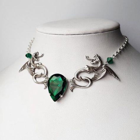 Ce collier de déclaration comporte un grand bijou en verre en forme de déchirure en forme de lait qui se trouve dans un réglage de tonalité argentée. Le bijou de verre est accompagné de serpents en laiton plaqué argent magnifiquement détaillés et de perles de cristal Swarovski. Le bijou est denviron