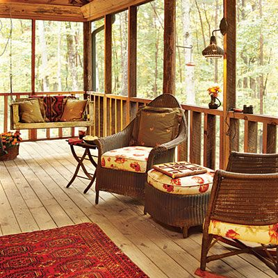 Hanging swing, sconces on posts, rug on floor, pretty cushions. Warm and inviting.