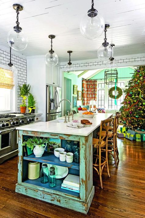 Island Time | When the kitchen opens into your family room, it's important for the decor to carry through. Here, the kitchen's colors worked their way into the decorations like the blue and red wreath and gold and green Christmas tree. #kitchenideas #holidaydecor