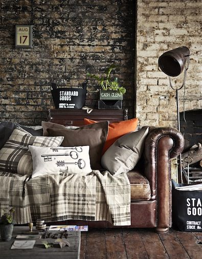 gorgeous exposed brick walls that are kind of dark and amazing leather couch / pillows