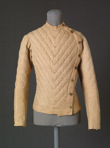 A fencing jacket with padded sections at the upper arms and chest in pale fawn linen;