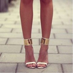 Gold and white strappy heels.