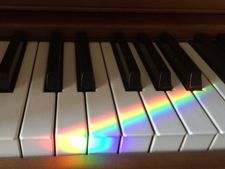 Rainbow piano keys illuminated by a prism beam from the Spectra rainbow sundial on the window sill